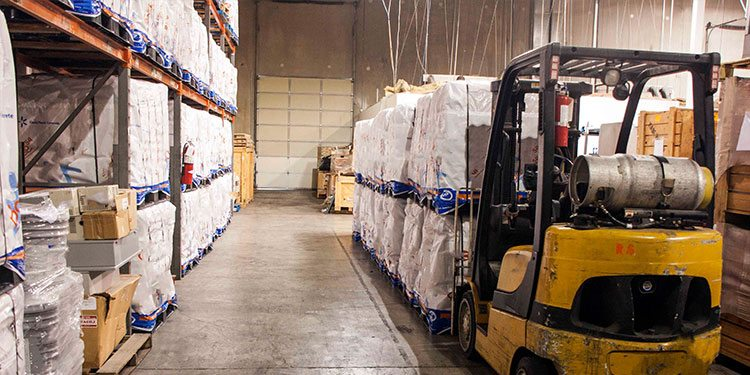 Image of a warehouse forklift transporting freight as part of a supply chain solution.