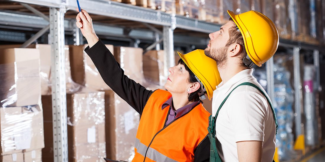 Warehouse engineer ordering to worker how to work